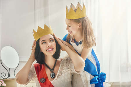 Happy loving family is preparing for a costume party. Mother and her child girl playing together. Beautiful queen and princess in gold crowns. Stock Photo - 61415134