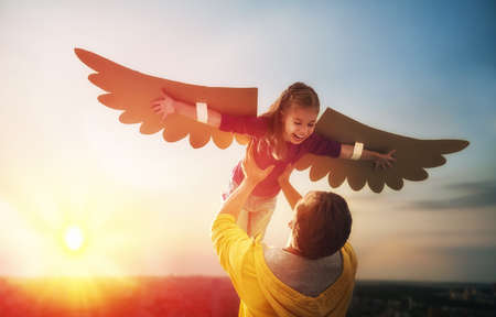 Father and his daughter child playing together. Little girl plays in the bird. Happy loving family having fun. Archivio Fotografico