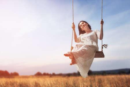 joven y bella mujer en un columpio en el día de verano al aire libre