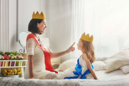 Gelukkig liefdevolle familie bereidt zich voor op een kostuum partij. Moeder en haar kind meisje samen spelen. Mooie koningin en prinses in gouden kronen. Stockfoto
