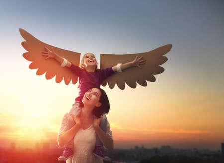 La madre y su hijo hija jugando juntos. Juegos de la niña en el ave. Feliz amante de la familia que se divierte.