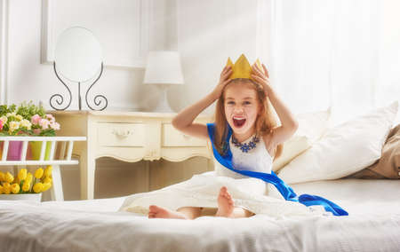 primp: Cute little girl in a princess costume. Pretty child preparing for a costume party. Beautiful queen in gold crown.