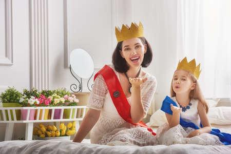 Amante de la familia feliz que se está preparando para una fiesta de disfraces. La madre y su niña niño jugando juntos. Hermosa reina y princesa en coronas de oro. Foto de archivo - 61415196