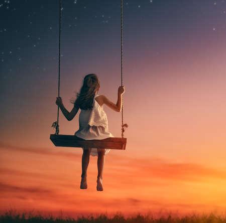 Menina feliz da criança no balanço no por do sol do verão