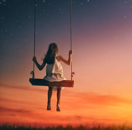 columpios: niña feliz niño en el oscilación en la puesta del sol del verano