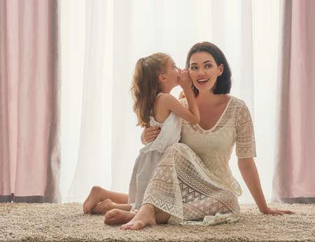 amante de la familia feliz. La madre y su hija juego muchacha niño y abrazos. Hija que susurra a la mamá un secreto.
