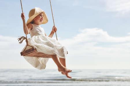 夏の日のスイングで幸せな子供女の子 写真素材
