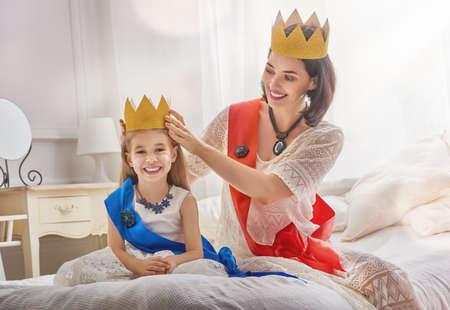 幸せな愛情のある家族は、仮装パーティーのために準備しています。母と彼女の子供の女の子一緒に遊んで。美しい女王と金の王冠の姫。