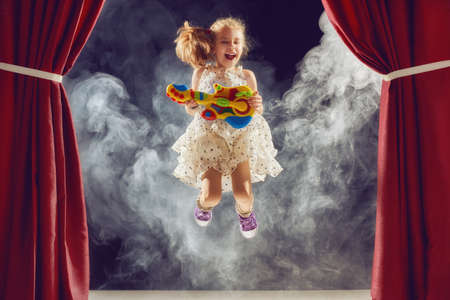 かわいらしい子供の女の子がステージでギターを弾きます。子供ロック ・ ミュージシャンになる夢。 写真素材