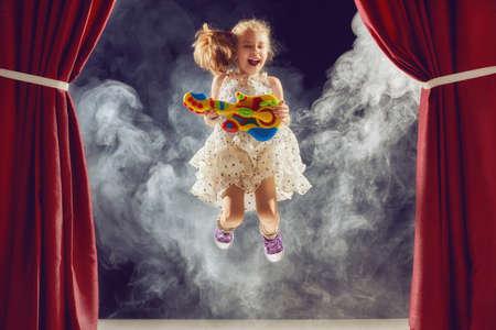 Leuk weinig kind meisje spelen gitaar op het podium. Kid droomt ervan om een rockmuzikant. Stockfoto