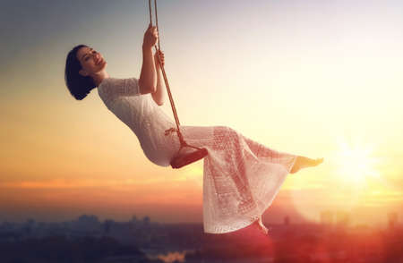 woman sunset: beautiful young woman on a swing on summer sunset outdoors