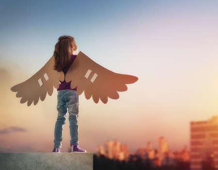 Holčička hraje venku. Dítě na pozadí západu slunce na obloze. Kid s křídly ptáka sny o létání.
