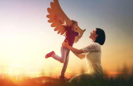 Madre e il suo bambino figlia giocare insieme. La bambina gioca l'uccello. Felice famiglia amorevole divertirsi.