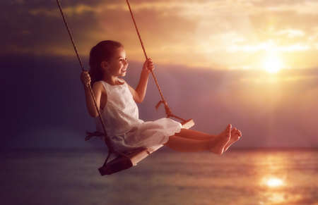 girl on swing: Happy child girl on swing in sunset summer