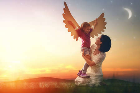 Mother and her daughter child playing together. Little girl plays in the bird. Happy loving family having fun. Stock Photo