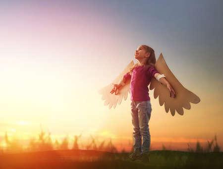 어린 소녀 야외한다. 일몰 하늘의 배경에 아이입니다. 비행 조류의 꿈의 날개를 가진 아이.