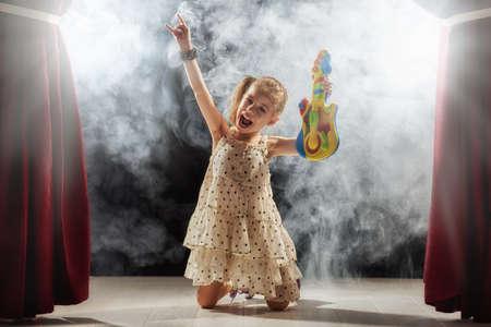 Nettes kleines Mädchen, Kind spielt Gitarre auf der Bühne. Kid träumt davon, ein Rockmusiker. Standard-Bild - 62741090