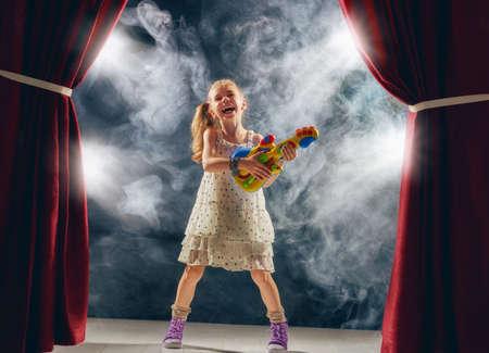 귀여운 작은 아이 소녀 무대에서 기타를 연주. 키드는 록 뮤지션이되는 꿈을 꾸며.