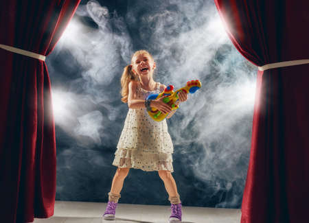 voices: Cute little child girl playing guitar on stage. Kid dreams of becoming a rock musician.