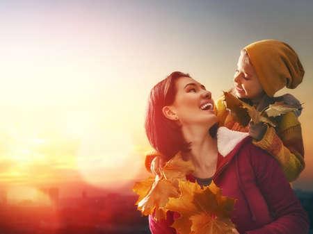 Mutter und ihr Kind Mädchen spielen zusammen auf Herbst Spaziergang in der Natur im Freien. Glückliche liebevolle Familie, die Spaß.