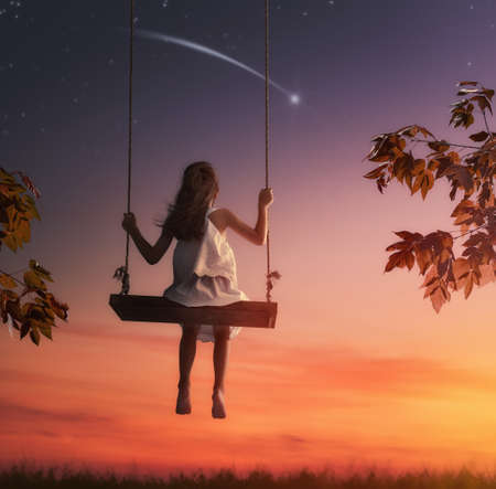 Happy child girl on swing in sunset summer. Kid makes a wish by seeing a shooting star. Stock Photo