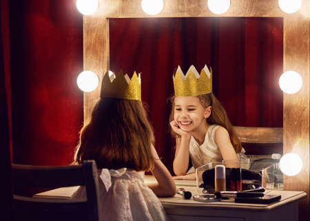 Cute little actress. Child girl in Princess costume on the background of theatrical scenes and mirrors. Imagens