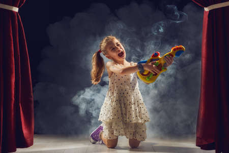 talent show: Cute little child girl playing guitar on stage. Kid dreams of becoming a rock musician.