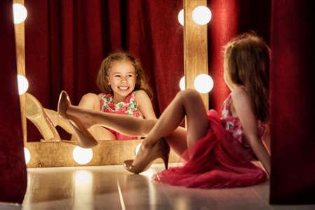 Nette kleine Fashionista. Glückliches Mädchen, Kind versuchen, auf Outfits und Mamas Schuhe am Spiegel.