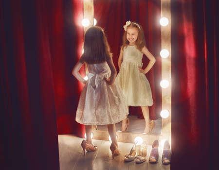 Carino fashionista. Ragazza felice del bambino provare su abiti e le scarpe della mamma guardando specchio.