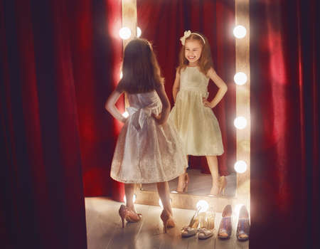 Cute little fashionista. Happy child girl try on outfits and mom's shoes looking at mirror. Foto de archivo