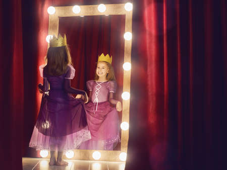 Cute little actress. Child girl in Princess costume on the background of theatrical scenes and mirrors. Stock Photo