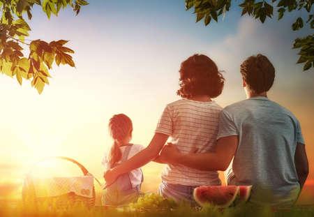Familia de picnic juntos. madre, padre e hija niña de jóvenes sentados juntos en la hierba verde en el parque de verano.