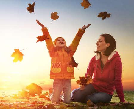 Moeder en haar kind meisje spelen samen op herfst wandeling in de natuur buiten. Gelukkig liefdevolle familie plezier. Stockfoto