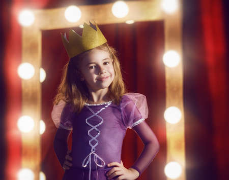 Cute little actress. Child girl in Princess costume on the background of theatrical scenes and mirrors. Banque d'images