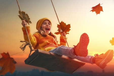 Niña feliz en el oscilación en la puesta del sol de otoño. Niño que juega en el otoño en el paseo por la naturaleza.