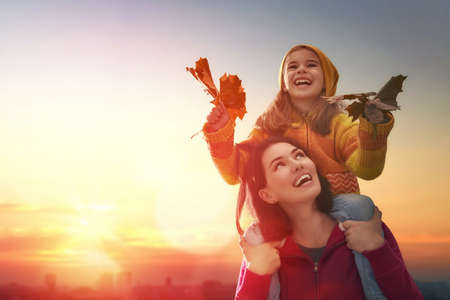 Mother and her child girl playing together on autumn walk in nature outdoors. Happy loving family having fun.