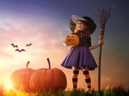 Fröhliches Halloween! Nette kleine Hexe mit einem großen Kürbis. Schöne junge Kind Mädchen draußen im Hexekostüm. Standard-Bild