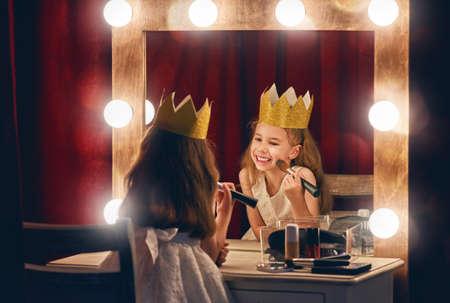 Roztomilá herečka. Dítě dívka v kostýmu princezny na pozadí divadelních scén a zrcadel.