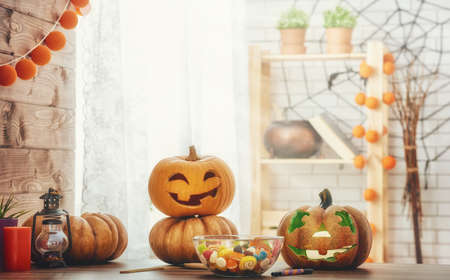 Happy halloween! Carving pumpkin on the table in the home. Happy family preparing for Halloween.