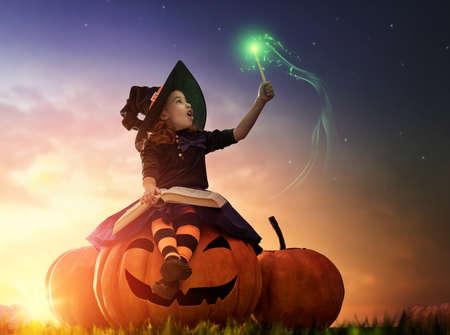 Fijne Halloween! Leuke vrolijke kleine heks met een toverstokje en boek van spreuken. Mooi kind meisje in heks kostuum zittend op de grote pompoen, bezwerende en lachen.