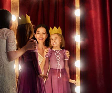 귀여운 작은 배우. 젊은 엄마와 그녀의 딸 연극 장면과 거울의 배경에 공주 의상 자식 소녀.