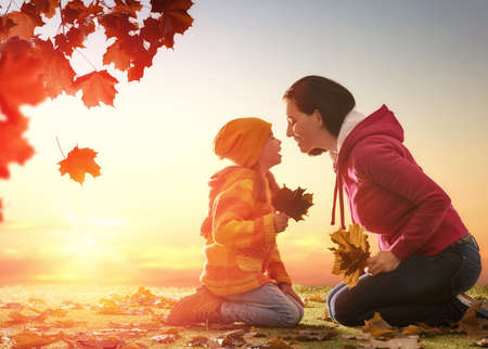 kids outside: Mother and her child girl playing together on autumn walk in nature outdoors. Happy loving family having fun.