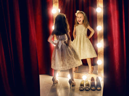 Cute little fashionista. Happy child girl try on outfits and moms shoes looking at mirror.