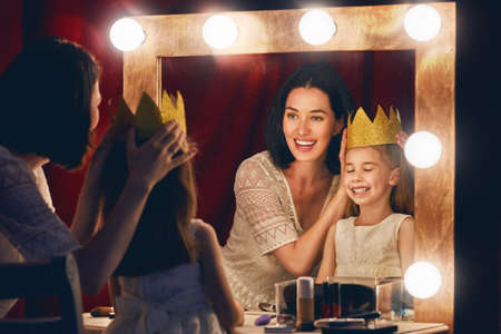 Happy loving family. Mother and daughter are doing makeup and having fun. Mother and daughter sitting at dressing table and looking at the mirror. Stock Photo