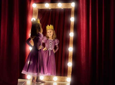 Carino attrice. Ragazza del bambino in costume principessa sullo sfondo di scene teatrali e specchi. Archivio Fotografico - 62778902