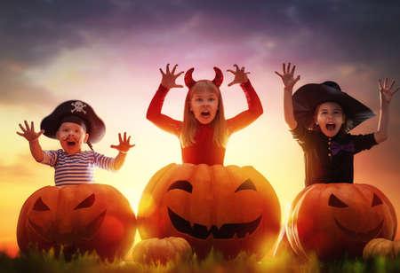 Gelukkig broer en twee zussen op Halloween. Grappige kinderen in carnaval kostuums die buitenshuis. Vrolijke kinderen en pompoenen op zonsondergang op de achtergrond. Stockfoto