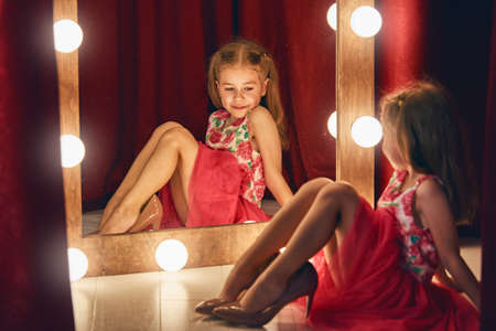 mirror: Cute little fashionista. Happy child girl try on outfits and moms shoes looking at mirror.