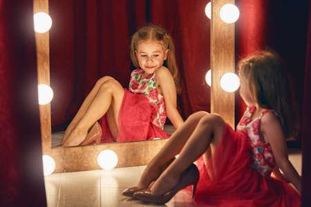 pequeño: pequeña fashionista lindo. Niña feliz probarse trajes y zapatos de la mama que mira el espejo. Foto de archivo