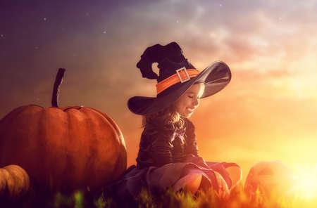 vestido de noche: ¡Feliz Halloween! pequeña bruja linda con una calabaza grande. chica hermoso del niño joven en traje de bruja al aire libre.