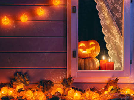 Happy halloween! The window of a house decorated for the holiday. Pumpkins, garland, candles and autumn leaves.